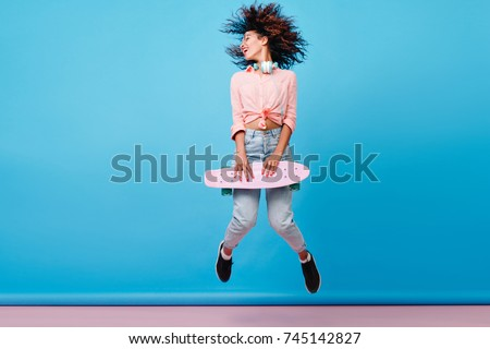 Indoor portrait of african lady with curly hairstyle jumping on blue background during photoshoot. Inspired female model in jeans and black sneakers posing with skateboard.