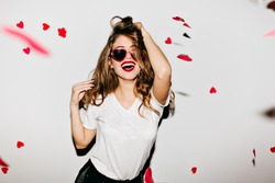 Indoor portrait of amazing caucasian female model in trendy t-shirt touching her long shiny hair. Laughing refined woman in sunglasses having fun with red confetti.
