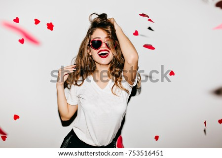 Indoor portrait of amazing caucasian female model in trendy t-shirt touching her long shiny hair. Laughing refined woman in sunglasses having fun with red confetti. #753516451