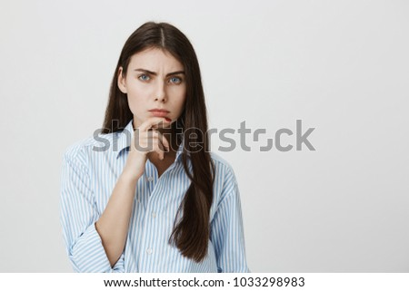 Indoor portrait of attractive european model holding hand near chin staring at camera with frowned eyebrows and serious face, expressing disbelief over gray background. Girl thinks boyfriend lies - Shutterstock ID 1033298983