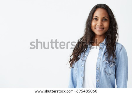 Indoor portrait of beautiful Afro-American brunette young woman smiling cheerfully, showing her white teeth to camera, feeling herself happy and carefree. #695485060