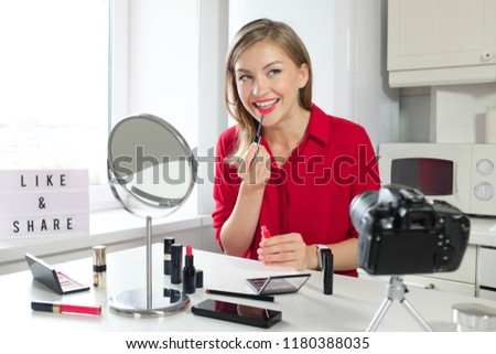 Indoor portrait of beautiful young European woman pictured at kitchen table where she is preparing to film video about cosmetics for her beauty blog, smiling as she is applying liquid lipstick to lips