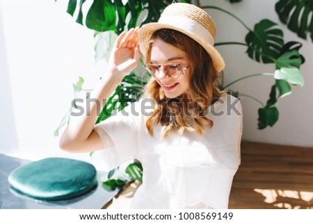 Indoor portrait of blissful curly girl wears straw hat with white ribbon chilling in room with big green plant. Amazing blonde young lady looking down while posing in stylish accessories with smile.