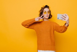 Indoor portrait of cute girl in soft knitted attire posing with peace sign. Photo of curly glamorous woman in sunglasses holding smartphone and making selfie.
