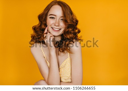 Indoor portrait of excited curly woman with trendy makeup. Ginger caucasian young lady smiling on yellow background.