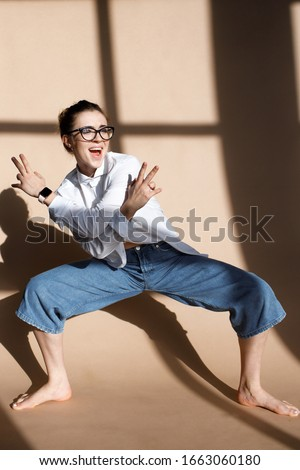 Indoor portrait of fashionable woman wearing wide jeans and glasses. Pretty girl have fun in studio. Fashion blogger concept. Spring fashion concept. beautiful model
