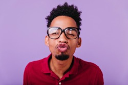 Indoor portrait of funny african man posing with kissing face expression. Close-up photo of carefree brunette boy fooling around on purple background.