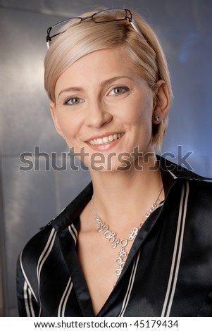Indoor portrait of happy young businesswoman at office, smiling.