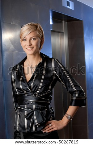 Indoor portrait of happy young businesswoman standing on office corridor, smiling.