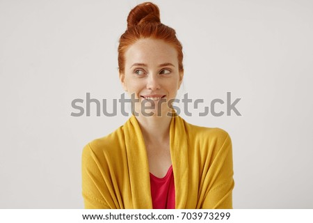 Indoor portrait of mysterious charming young European gimger female with hair knot looking sideways with enigmatic smile, biting her lips while planning surprise birthday party for her husband Photo stock ©