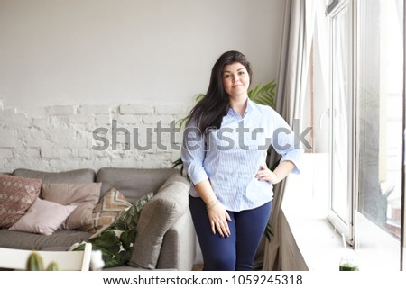 Indoor portrait of overweight plus size young female with loose black hair and charming smile standing in cozy living room interior by the window, holding hand on her waist, looking at camera