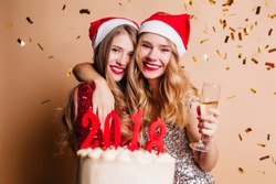 Indoor portrait of two enthusiastic girls in santa claus hats having fun at christmas party. Blonde young ladies holding delicious new year cake and laughing on confetti background.