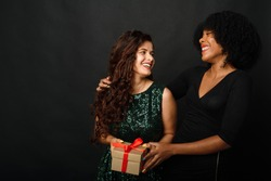 Indoor portrait of two happy best friends sisters women, ready for holiday party, holding bright gifts and presents, wearing bright dresses