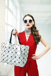 Indoor portrait of young beautiful fashionable woman posing in white interior. Model wearing stylish round sunglasses, elegant red clothes, holding big silvery bag. Female fashion concept. Waist up