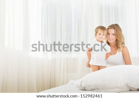 indoor portrait of young happy mother and baby child in bed at home in the morning