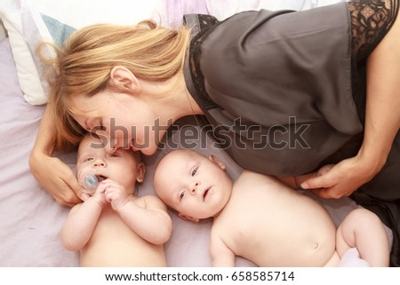 indoor portrait of young happy smiling mother with her twin babies at home