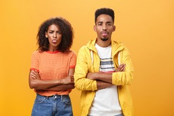 Indoor shot of african american siblings being displeased and annoyed showing bad tempber behaving childish sticking out tongue standing together with crossed hands on chest over orange background
