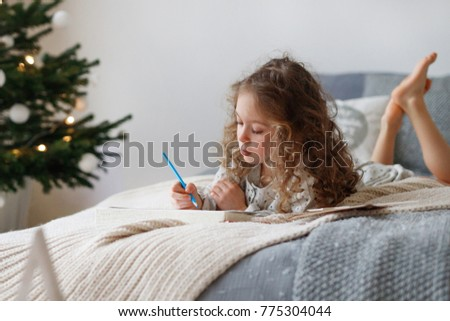 Indoor shot of attentive pretty small girl writes letter to Santa Claus before Christmas, thinks what present she expects, wants all dreams and wishes come true, lies on comfortable bed indoor. #775304044
