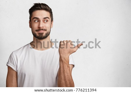 Indoor shot of attractive young male model wears casual white t shirt indicates with thumb aside, poses against concrete wall with copy space for your advertising content or promotional text