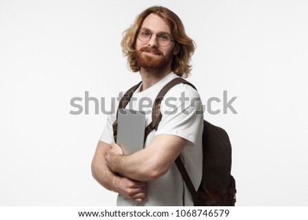 Indoor shot of bearded male university student standing isolated on gray background with closed laptop in hands with open positive smile, expressing enthusiasm and initiative #1068746579