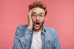 Indoor shot of bearded stylish man has trendy hairdo, looks with great surprisment, as realizes his big failure, has no right or chance for improvement. Handsome young male with shocked face