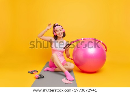 Indoor shot of carefree young Asian woman enjoys favorite playlis holds mobile phone wears stereo headphones dressed in activewear sits on mat trains at home uses fitness ball hula hoop expander