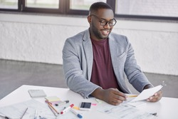 Indoor shot of cheerful African American male enterpreneur sits at table surrounded with papers, studies financial report, rejoices raising sales and acheivement goals. Black businessman at work