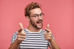 Indoor shot of cheerful bearded man in spectacles and casual clothes indicates happily at you, chooses to compete, has positive expression. Handsome clever student makes choice, isolated on pink wall