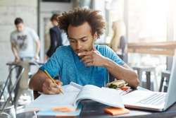 Indoor shot of dark-skinned male student with African hairstyle wearing blue casual T-shirt sitting at university canteen eatting hamburger reading attentively book underline necessary information