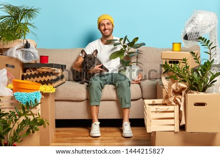 Indoor shot of delighted carefree house owner sits on couch and hugs pet, rests in own apartment, being in high spirit, celebrates move, has fun at home much household stuff around. Relocation concept