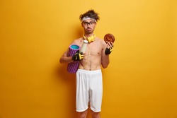 Indoor shot of displeased sportsman feels temptation to eat junk food, carries foam roller, wants to have perfect body, wears stereo headphones around neck shorts, headband, sport gloves, does workout