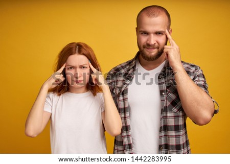 Indoor shot of frustrated thoughtful adult woman and man keep fingers on temples, try to concentrate on difficut question, stand closely, being deep in thoughts, isolated on yellow background #1442283995