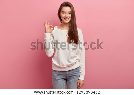Indoor shot of good looking brunette woman customer shows great sign, satisfied with good quality of product, dressed in casual clothes, models against pink background. Girl demonstrates zero sign