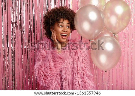 Indoor shot of good looking female with Afro haircut, looks aside with happy expression, notices guests, holds bunch on helium balloons, wears rosy fur coat, celebrates anniversary birthday.