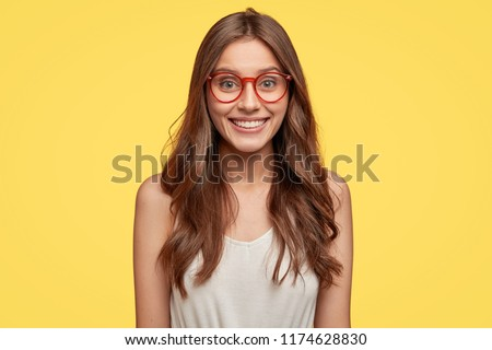 Indoor shot of good looking young Caucasian woman has broad smile, being in good mood after date with boyfriend, wears round glasses, looks directly at camera, poses against yellow studio wall.