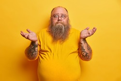 Indoor shot of hesitant bearded man with excess weight shrugs shoulders and stands unaware, has thick beard, big beer belly, dressed in yellow t shirt, round spectacles, faces difficult choice.
