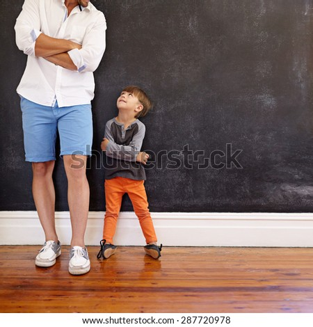 Indoor shot of little boy and his father standing with hands folded against black wall. Father and son looking at each other with copy space. Son imitating his father\'s pose.
