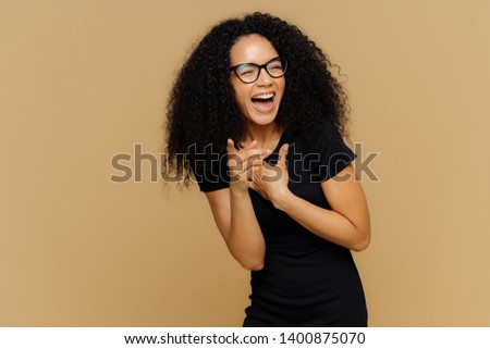 Indoor shot of overjoyed female laughs out loudly, notices funny scene, points at camera, keeps mouth widely opened, wears transparent glasses, casual black t shirt, isolated over brown background