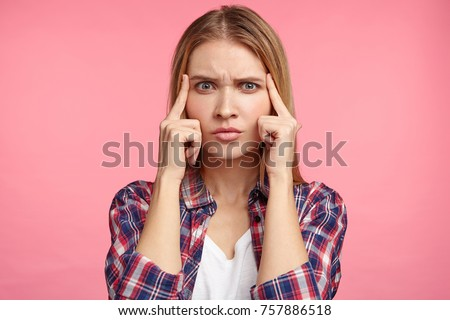 Indoor shot of pensive female model tries to concentrate or remember important information, had bad memory, has thoughtful expression. Female student answers on exam, recollects topic in mind Stockfoto ©