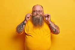 Indoor shot of pleased plump man twirls mustache, boasts of thick beard, stands with closed eyes, smiles pleasantly, has tattooed arms dressed in yellow clothes wears round small glasses poses indoor