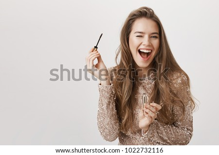 Indoor shot of positive attractive caucasian woman winking and smiling broadly while holding mascara and applying it, standing in evening dress over gray background. Girl gets ready to nightclub #1022732116