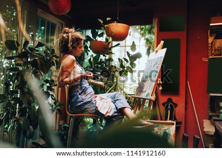 Indoor shot of professional female artist painting on canvas in studio with plants. #1141912160