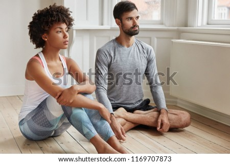 Indoor shot of relaxed couple sit on floor, meditate and try to relax after active hard working day, look thoughtfully into distance, enjoy peaceful atmosphere at home. People and relaxation concept #1169707873