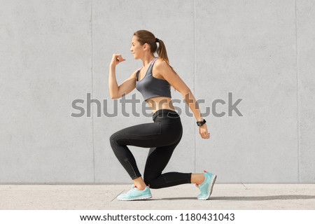 Indoor shot of self determined woman with pony tail, stands on one knee, warms up before cardio training, wears tanktop, leggings, sneakes, goes in for sport regularly, isolated over grey background #1180431043