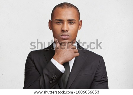 Indoor shot of serious mixed race male magnat dressed in elegant black suit, looks confidently into camera, waits for business partner as going to sign indemnity contract, isolated over white wall #1006056853