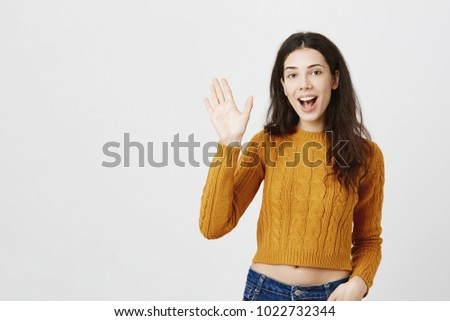 Indoor shot of sexy european female wearing stylish cropped top, saying hi and waving with hand at camera, standing over gray background. Girlfriend meets with friends to hang out