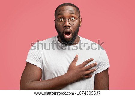 0be34edf47 Indoor shot of shocked plump dark skinned young male wears casual white t  shirt and spectacles