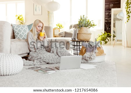 Indoor shot of sick young woman sitting on carpet covered with a blanket in the modern living room, holding cup. Notepads, laptop and documents on the floor.