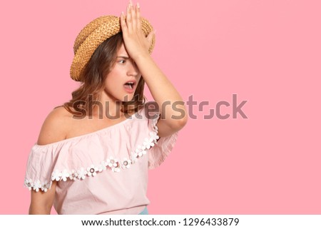 Indoor shot of stressful woman keeps hand on forehead, recalls something in mind, wears headgear, forgets to buy something necessary for vacation, isolated over pink wall with empty space aside