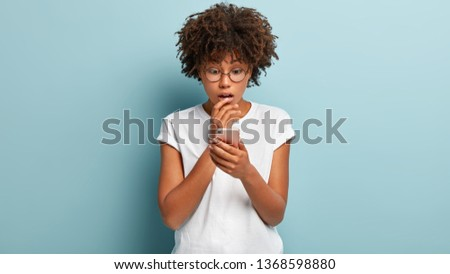 Indoor shot of stunned Afro American woman focused in cell phone, reads stunning terrible news, uses modern app, wears spectacles for vision correction isolated against blue background has missed call